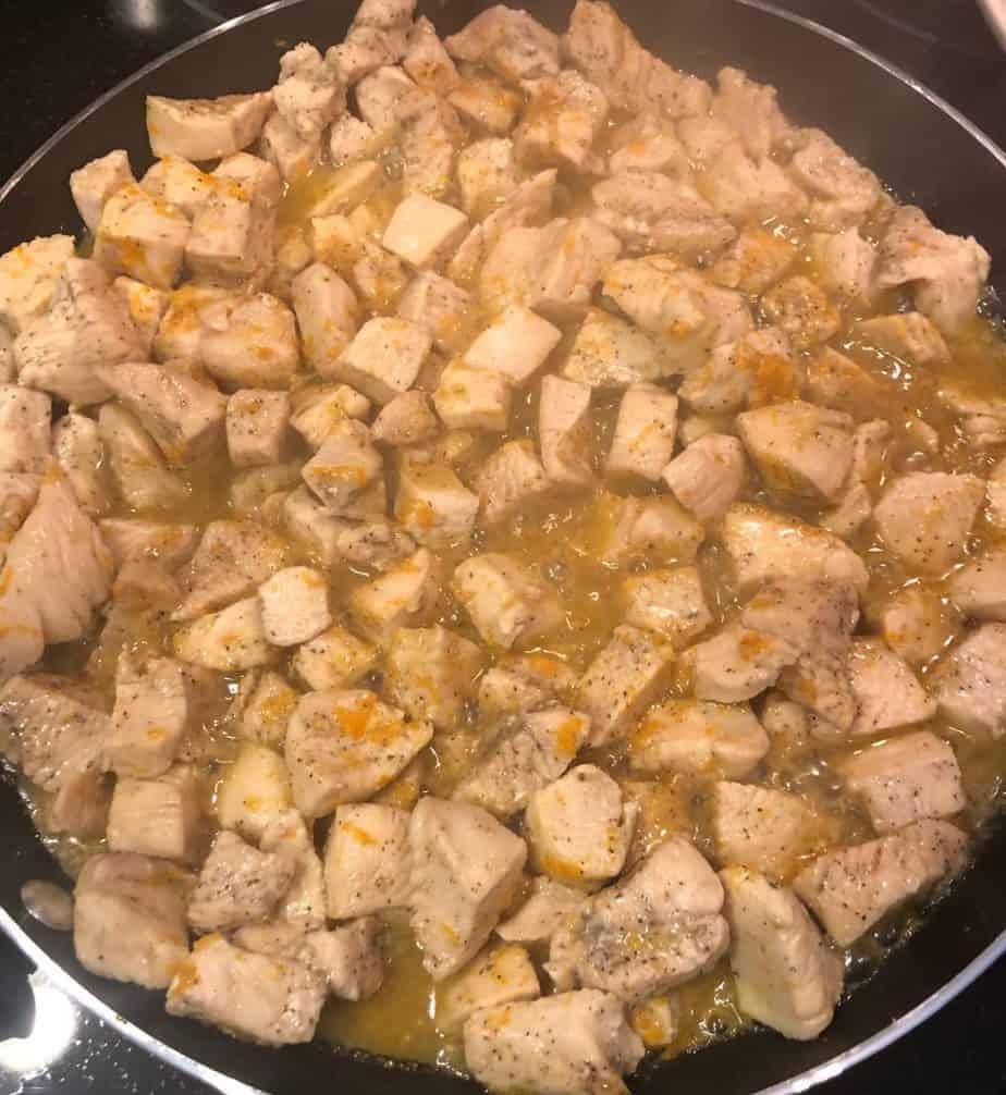 Chicken cooking in a sauté pan with lemon zest, orange zest and fruit juices.