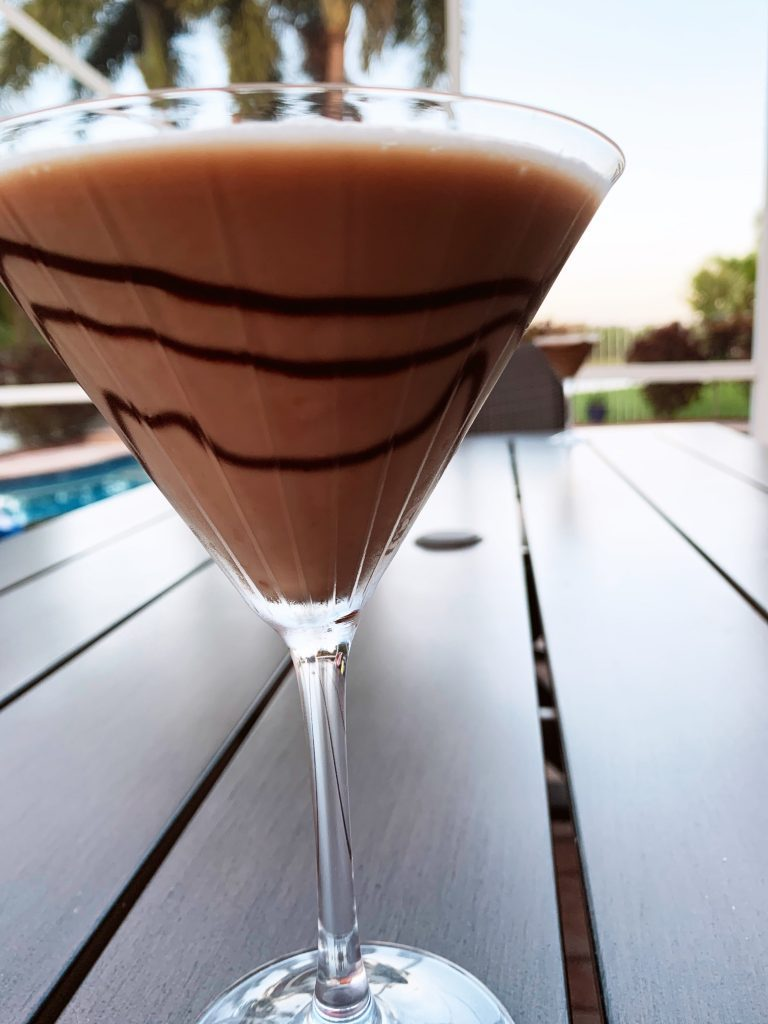 Almond Joy Martini in a glass on a table outside