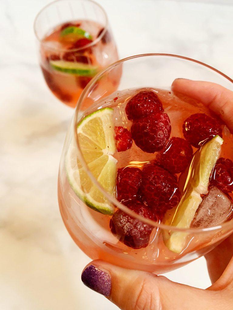 raspberry lime rosé sangria in 2 wine glasses with ice