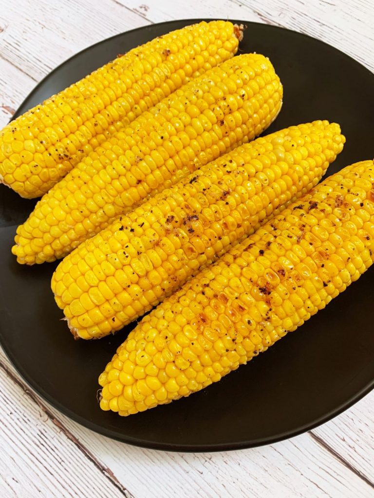 4 ears of oven roasted corn on the cob on a black plate